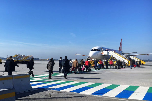 Pedestrians walking safely to plane in Porto Airport